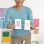 Female teacher holding up flash cards — Stock Photo