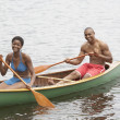African couple paddling canoe — Stock Photo