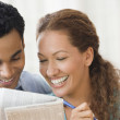 Hispanic couple reading newspaper - Stock Photo