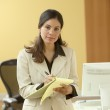 Portrait of businesswoman writing on legal pad — Stock Photo
