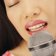 Stock Photo: Close up of Asian woman singing into microphone