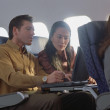 Young woman and man using laptop on airplane — Stock Photo