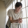 Young man laughing on a ladder - Stock Photo
