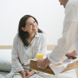 Hispanic man bringing breakfast to wife in bed — Stock Photo