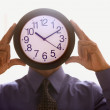 Businessman holding a clock before his face - Stock Photo