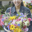 Asian woman holding flowers in basket — Stock Photo