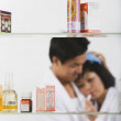 Portrait of sick Asian woman through medicine cabinet — Stock Photo