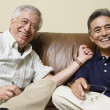 Portrait of elderly men sitting on the couch laughing — Stock Photo