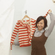 图库照片: Young womtrying on sweater in fitting rooms
