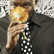 Young man smelling yellow flower — Stock Photo