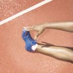 Female track athlete stretching — Stock Photo