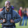 Young backpacker smiling for the camera outdoors — Stock Photo
