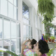 Mother and daughter looking out window of greenhouse — Stock Photo