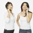 Studio shot of Asian mother and adult daughter talking on cell phones — Stock Photo