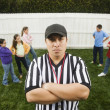 Hispanic referee between groups of girls and boys — Stockfoto