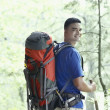 Young man backpacking in a forest — Stock Photo