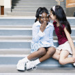 Two girls whispering on school stairs — Stock Photo
