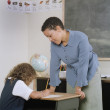 Stock Photo: Teacher helping school girl write