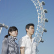 Foto Stock: Young couple posing by Ferris wheel