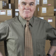 Businessman standing in warehouse — Stok fotoğraf