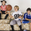 Group of children in sports gear on the sofa - Zdjęcie stockowe