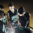 Girls basketball team in huddle - Stock Photo