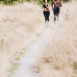 Couple jogging on gravel path — Stock Photo