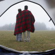 Indian couple wrapped in blanket at campsite — Stock Photo