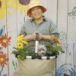 Senior woman holding gardening basket with flowers and dog — Stock Photo