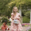 Young girl with Easter basket in garden — Stok fotoğraf