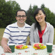 Portrait of Mixed Race couple at picnic table - Stock Photo