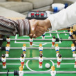 Stock Photo: Shaking hands over foosball table