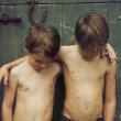 Two young brothers with arms around each other next to barn — Stock Photo