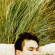 Asian man sleeping in dune grass — Stock Photo