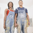 Portrait of couple in overalls painting -  
