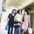 Three young women smiling walking together holding shopping bags — Photo