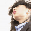 Low angle view of businesswoman with hair blowing in wind — Stock Photo