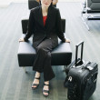 Woman with suitcase sitting at airport — Stok fotoğraf