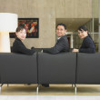 Stock Photo: Businesspeople sitting in lobby