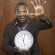 Stock Photo: Portrait of man holding clock