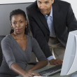 Portrait of man and woman at desk with computer — Stock Photo
