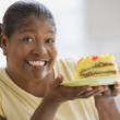 Middle-aged African woman smiling and holding up a piece of cake — Stok fotoğraf