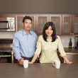 Stock Photo: Young couple posing for the camera in their kitchen