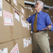 Businessman in warehouse looking at returned packages — Stock fotografie