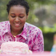 African woman blowing out birthday candle — Stock Photo