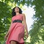 ショッピング バッグの公園で若い女性の低角度のビュー — ストック写真