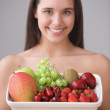 Portrait of teenage girl holding plate of fresh fruit — Stockfoto