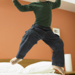 Young boy jumping on bed — Stock Photo