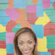 Young woman posing in front of a colorful wall — Stock Photo
