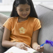 Stock Photo: Young girl writing with a feather pen